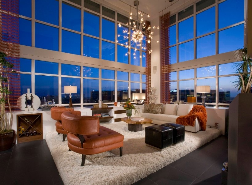 This formal living room offers a comfy set of seats along with a gorgeous ceiling light, surrounded by glass windows.