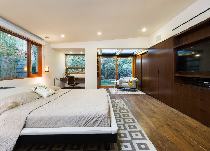 Large primary bedroom with hardwood flooring and a hardwood wall. The room has a large bed setup with a widescreen TV in front, along with a built-in desk in the corner. The room has glass windows and a glass door.