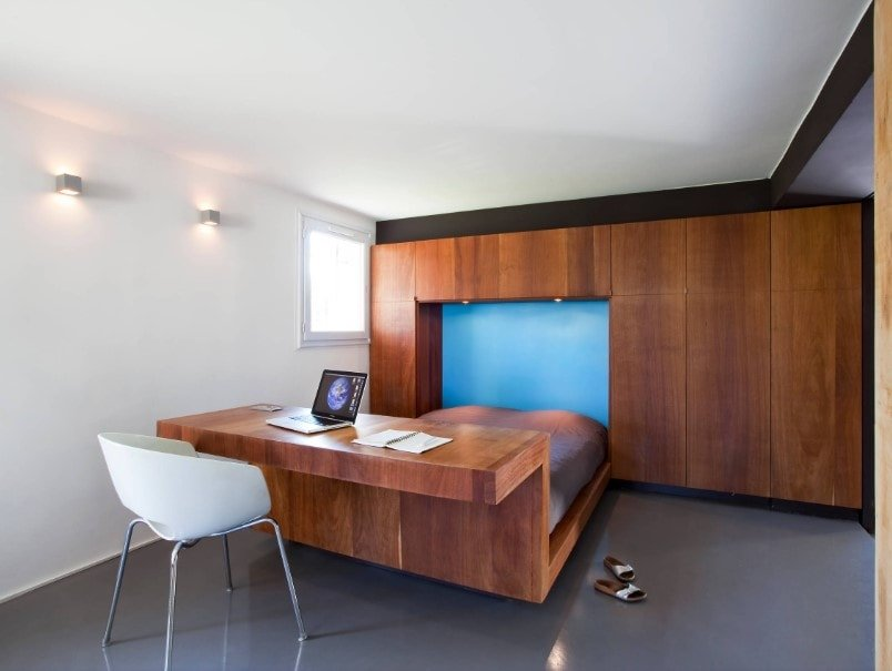 Contemporary primary bedroom with a built-in bed frame together with a built-in desk connected with to the bed's frame. The room features white walls and ceiling, along with dark gray tiles flooring.