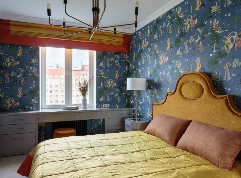 Small primary bedroom surrounded by blue decorated walls. The room has a built-in desk with drawers, along with a large elegant bed setup.