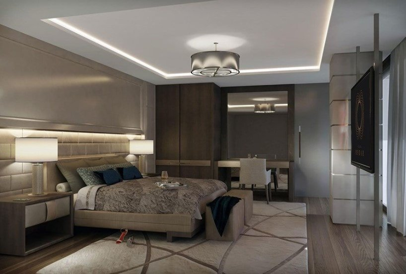Modern primary bedroom featuring a white tray ceiling and hardwood flooring topped by a classy area rug. The room offers a modish bed setup lighted by stylish table lamps on both sides.