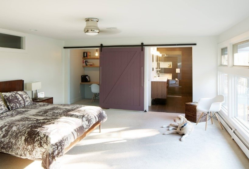 This primary bedroom boasts a bathroom with a shower and tub combo along with a built-in desk with shelving that can be closed with sliding doors. The room also offers a stylish bed setup with white carpet flooring.