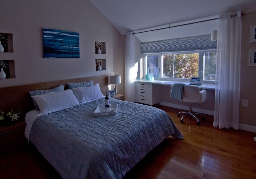 A focused shot at this primary bedroom's comfy bed lighted by a table lamp on the side, along with a built-in study desk near the windows.