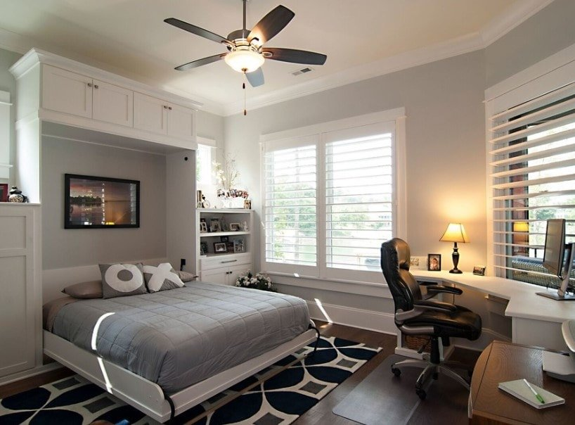 Primary bedroom featuring gray walls and hardwood floors topped by a stylish area rug. This bedroom has a TV on the wall, just above the bed setup along with a curved built-in desk lighted by a table lamp.
