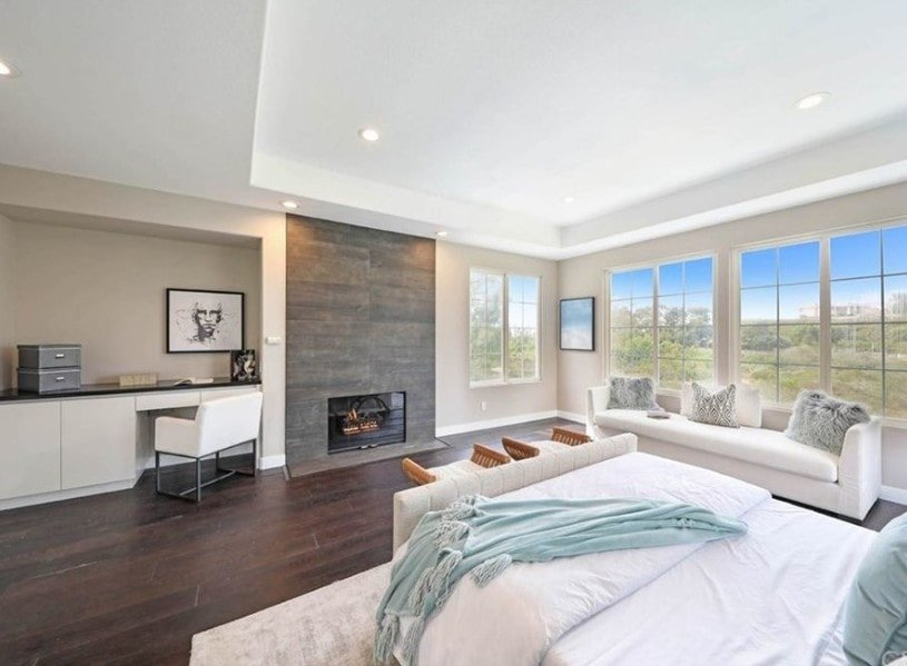 A spacious primary bedroom featuring a white tray ceiling and hardwood flooring, along with a white couch by the windows. The room also has a comfy white bed, a modern fireplace and a built-in desk on the side.