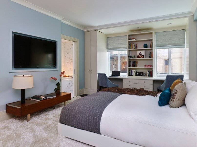 This primary bedroom features a sky blue wall with a large widescreen TV on the wall. The room has a large comfy bed and has two built-in study desks, with built-in shelving in between.