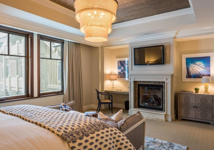 Primary bedroom featuring a classy bed lighted by a gorgeous ceiling light hanging from the tray ceiling. The home offers a fireplace and a TV, alongside the built-in study desk lighted by a table lamp.