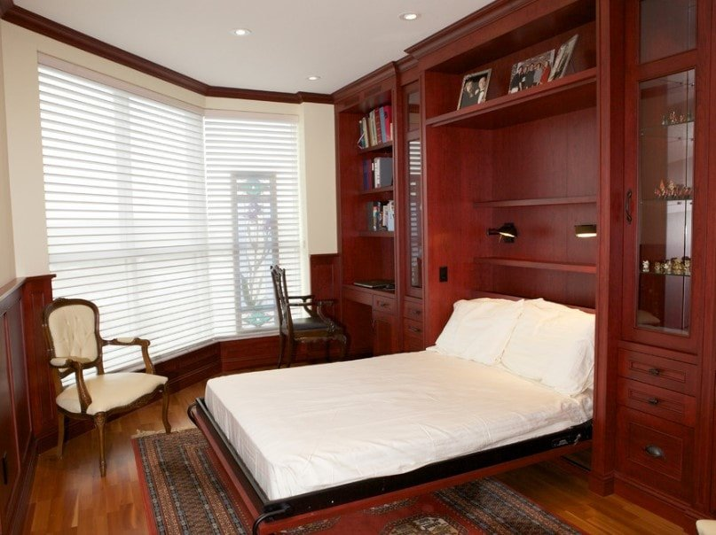 Brown primary bedroom with a built-in bed setup lighted by wall lights, along with built-in cabinetry, shelving and desk. The room also features hardwood flooring topped by an area rug.