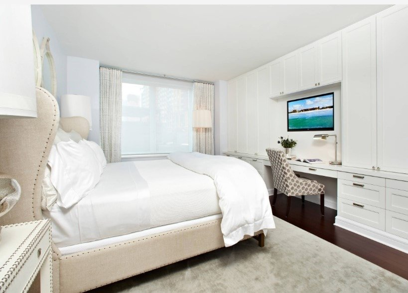 Primary bedroom featuring a classy bed setup with a TV in front, just above the built-in desk with drawers. The room is surrounded by white walls and a white ceiling.
