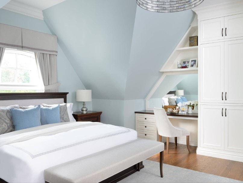 Primary bedroom featuring a lovely white bed along with a custom ceiling and hardwood flooring. There's a built-in desk on the side, together with built-in shelving and reach-in closet.