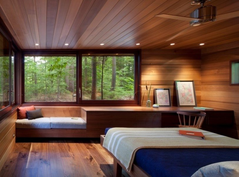 Primary bedroom boasting gorgeous wooden walls and ceiling, together with hardwood flooring. The room also offers a built-in seat by the window and a built-in study desk on the side.