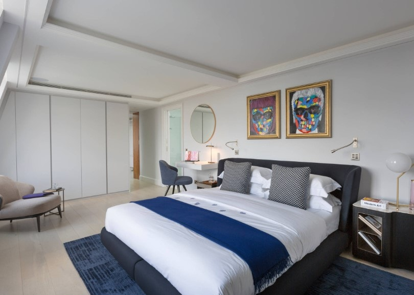 Primary bedroom with a modish bed setup on top of a stylish area rug covering the beige hardwood flooring. There's a built-in makeup desk on the side of the bed as well.