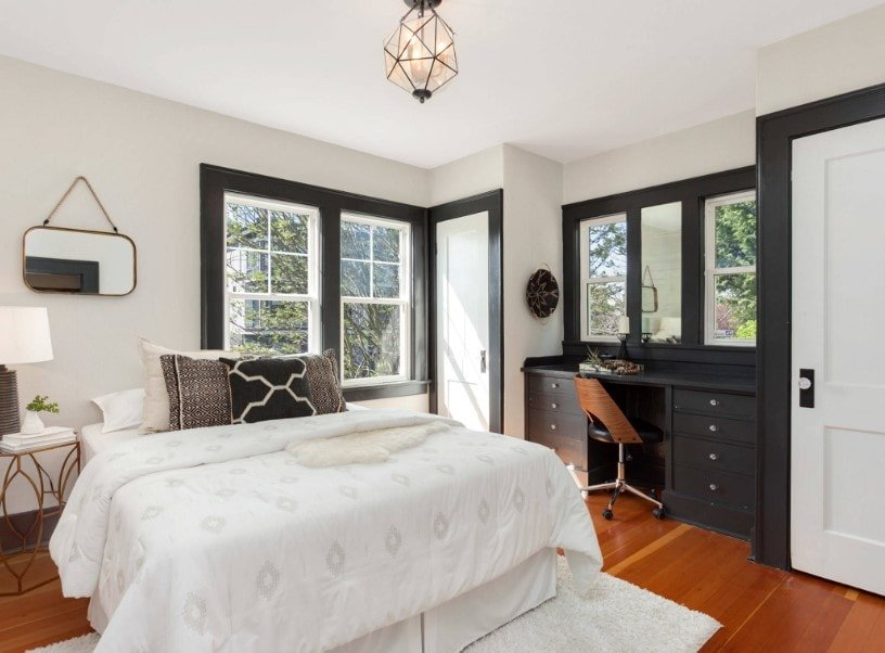 Primary bedroom with hardwood floors and white walls. The room has a comfy bed lighted by a white table lamp and has a built-in makeup desk with drawers on the side.