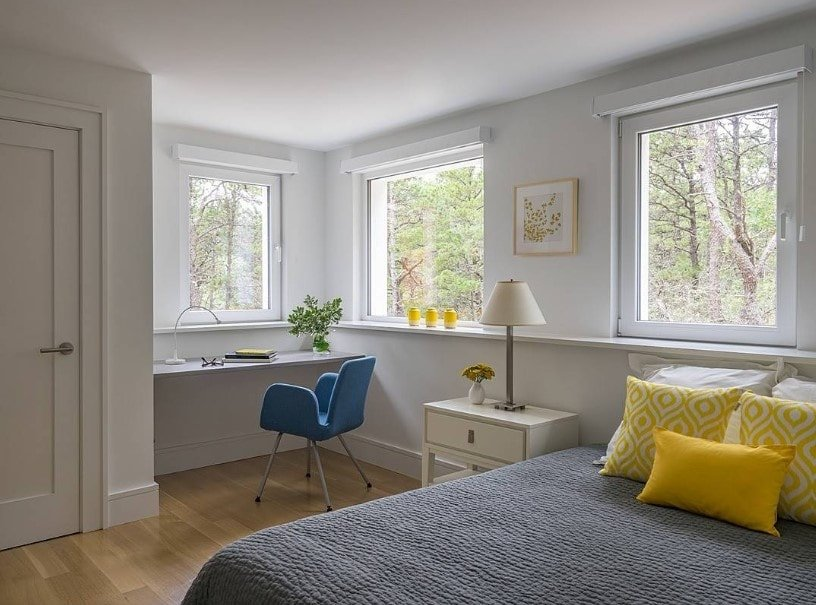 This primary bedroom offers a bed with a yellow accent with a bedside table featuring a table lamp. There's a built-in study desk on the side by the windows.