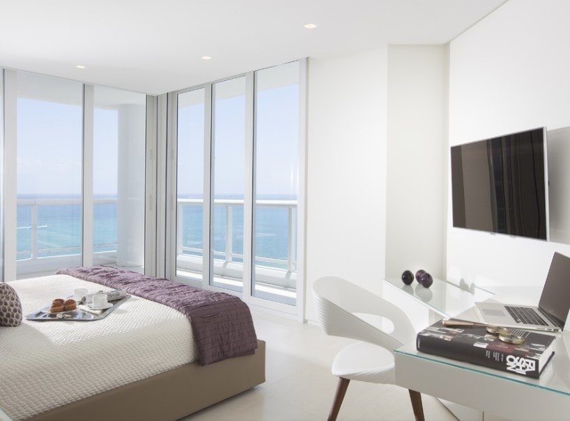 White primary bedroom featuring carpeted flooring and glass windows. The room offers a large flat-screen TV on the wall along with a built-in desk on the side.