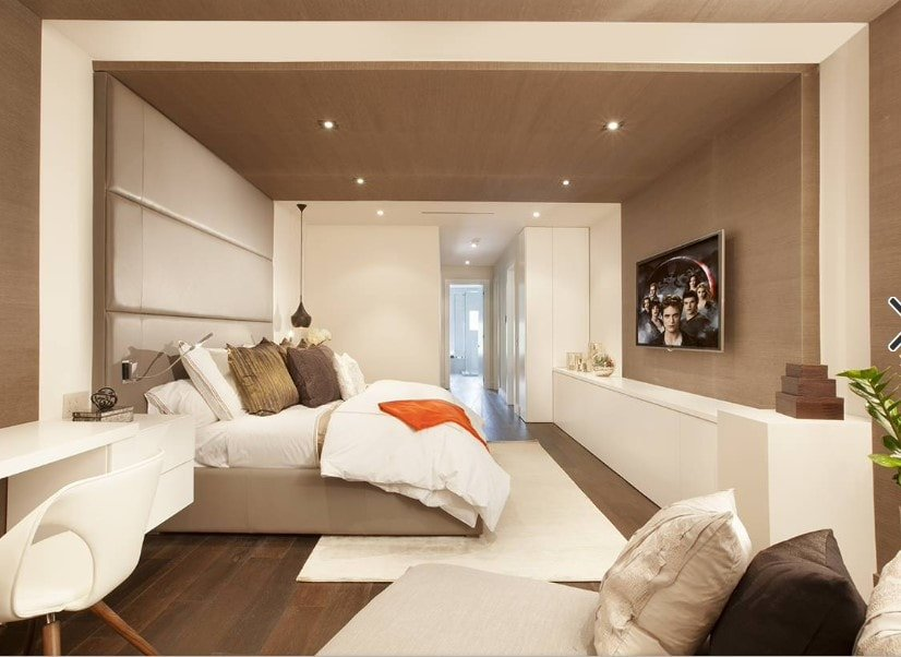 A spacious modern primary bedroom with a brown ceiling and hardwood flooring. The room offers a large cozy bed and a widescreen TV set in front of it. The room also has a sitting chair and a white built-in desk.