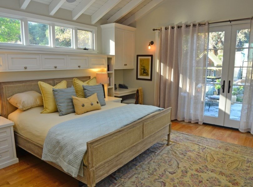 Primary bedroom boasting a charming bed lighted by two table lamps and has a small built-in desk with shelving on the side.