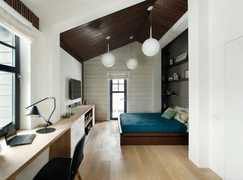 A spacious primary bedroom featuring a custom shed ceiling lighted by white pendant lights. The area features hardwood floors and white walls, together with a nice bed setup with built-in shelves, a widescreen TV set in front and a built-in study desk by the window.