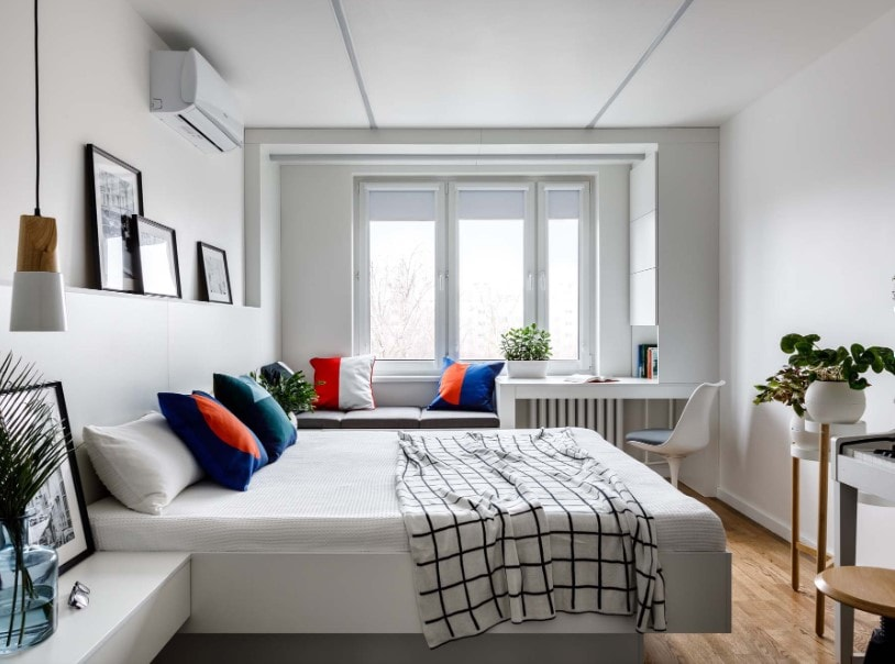 Primary bedroom featuring a white ceiling, white walls and hardwood flooring. This room offers a nice white bed setup with two built-in bedside tables, together with a built-in study desk by the window.