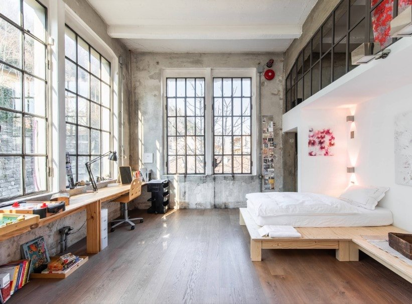A spacious primary bedroom featuring hardwood flooring and a tall ceiling. The room has a simplistic bed setup along with a built-in study desk.
