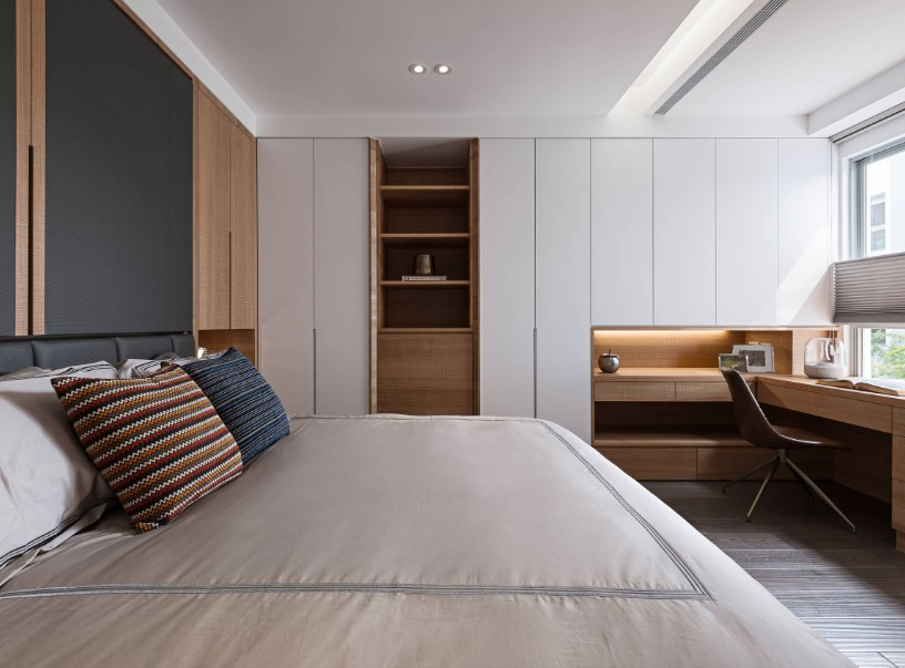 This primary bedroom offers a large cozy bed and a built-in study desk on the side near the glass window.
