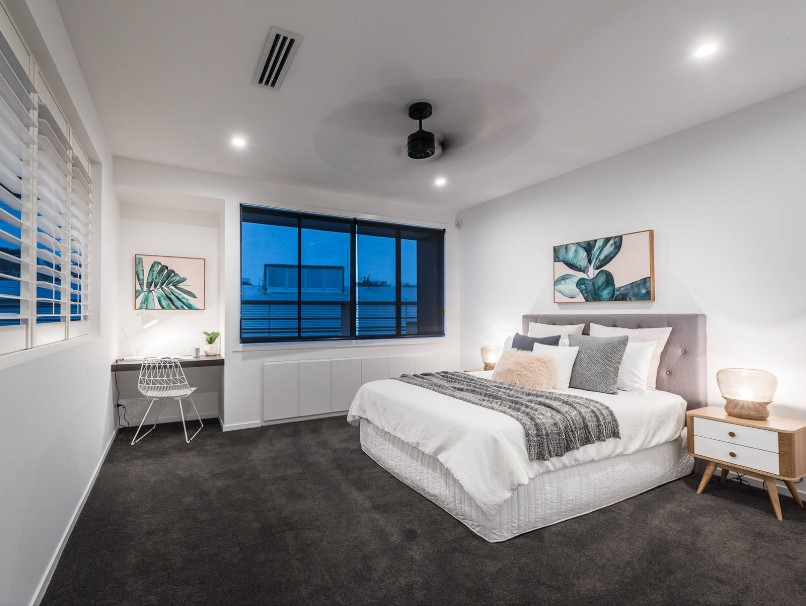 This primary bedroom features white walls and ceiling, along with dark gray carpet flooring. The room has a modern bed and a built-in desk on the side.
