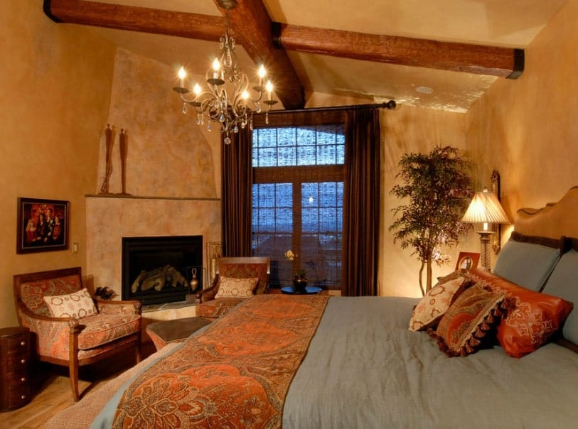 Primary bedroom with brown walls and a shed ceiling with exposed beams. The room offers a comfy bed and a fireplace with a sitting area, lighted by a glamorous chandelier.
