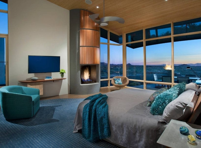 Contemporary primary bedroom featuring a tall shed ceiling and glass windows overlooking the stunning city view. The room offers a nice bed with a TV in front, along with a fireplace.
