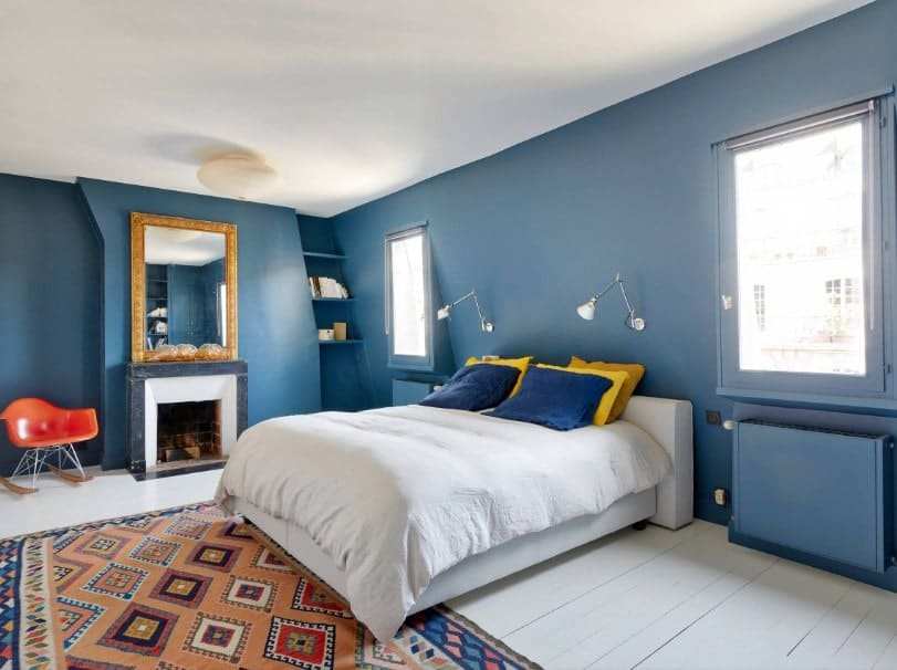 Primary bedroom with blue walls and a white ceiling. It features a large comfy bed along with a fireplace on the side.