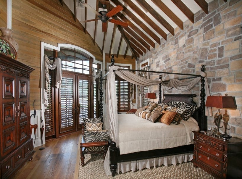 Primary bedroom featuring a wooden wall and a stone wall, along with hardwood flooring and a shed ceiling with beams. The room offers a classy bed and cabinetry.