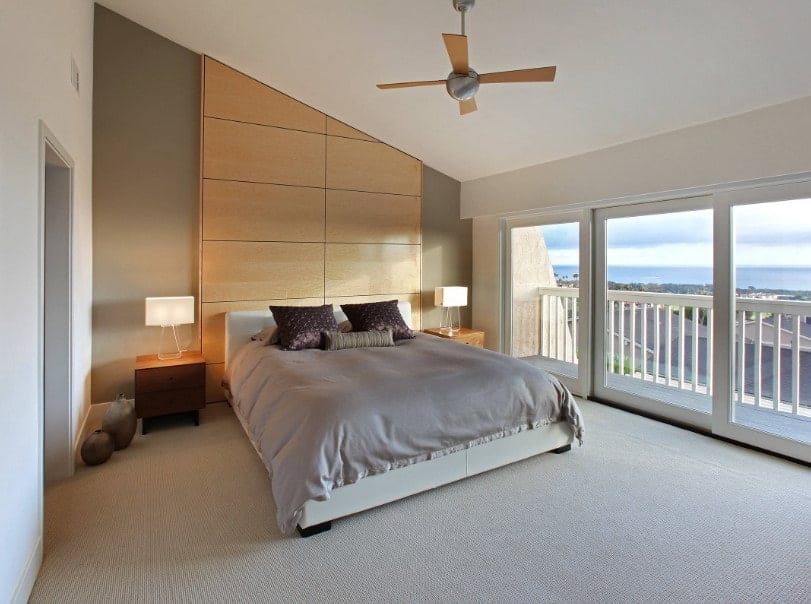 A primary bedroom with a comfortable bed setup lighted by table lamps on both sides. The room features a shed ceiling and carpeted flooring, along with a private balcony area.