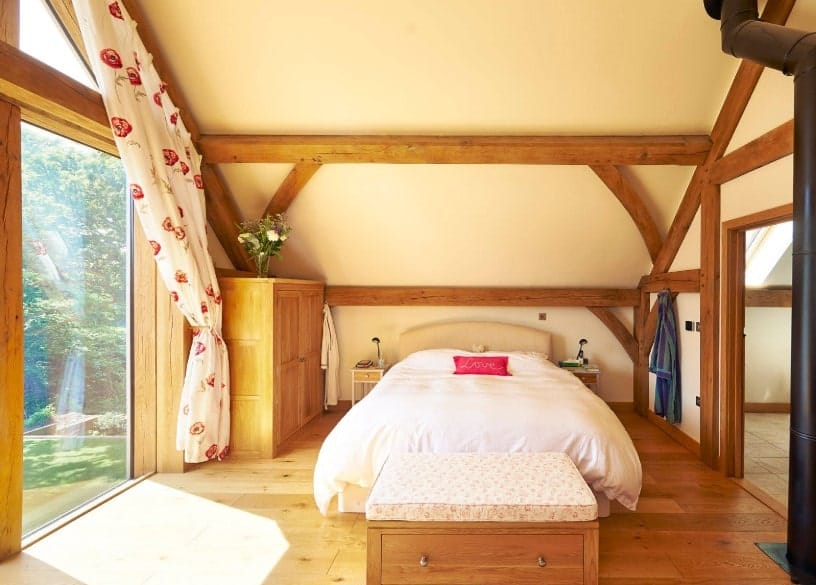 Primary bedroom featuring a shed ceiling and a large glass window, along with hardwood flooring. The room has its own bathroom.