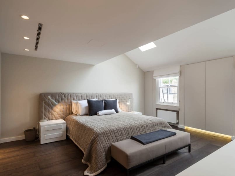 Primary bedroom featuring a modish bed setup. The room features hardwood flooring, white walls and a white shed ceiling with a skylight.