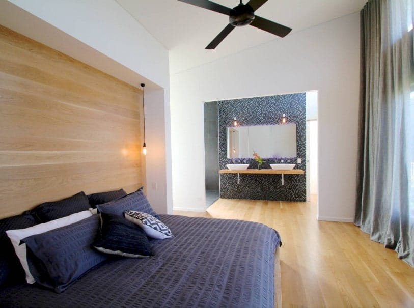 A spacious primary bedroom with a modern bed setup surrounded by white walls, hardwood floors and a shed white ceiling. The room also offers its own bathroom.