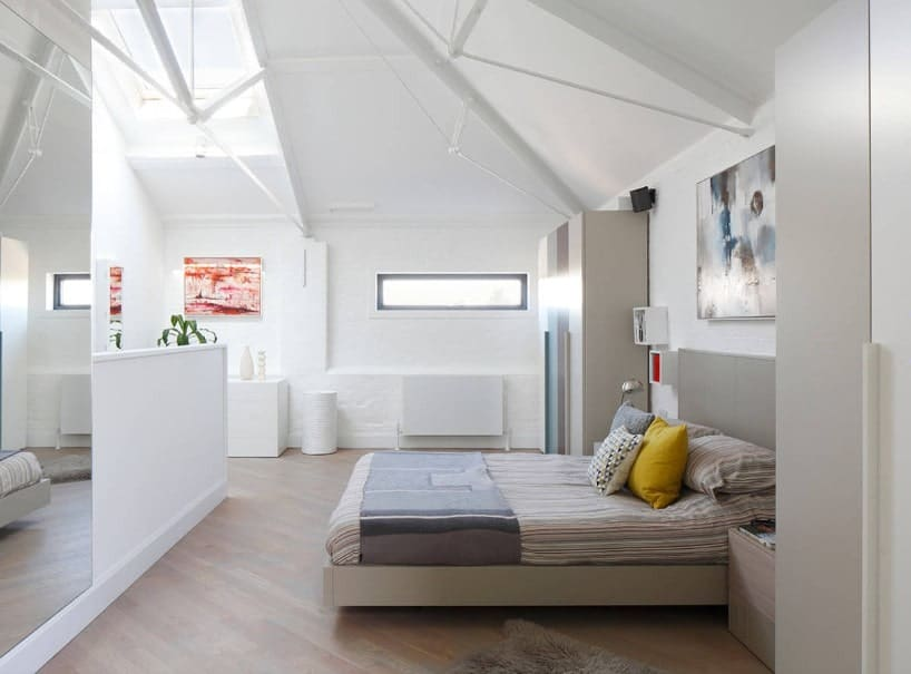A spacious primary bedroom with hardwood floors, white walls and a white shed ceiling with a skylight. The room offers a large cozy bed.