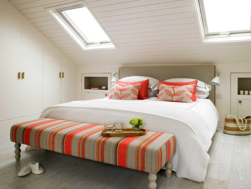 A focused shot at this primary bedroom's cozy bed with an orange accent. The room features a shed ceiling with skylights.