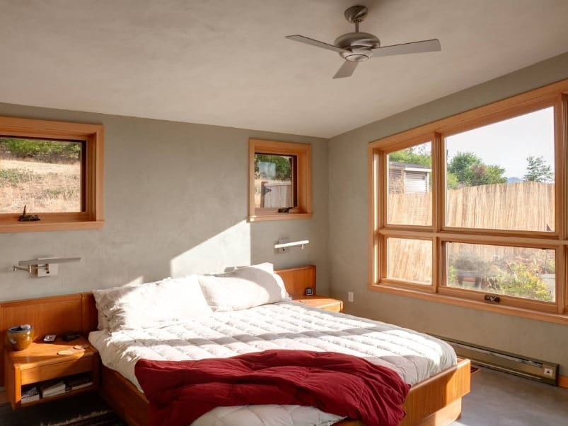 A focused shot at this primary bedroom's cozy bed with wooden built-in bedside tables on both sides.