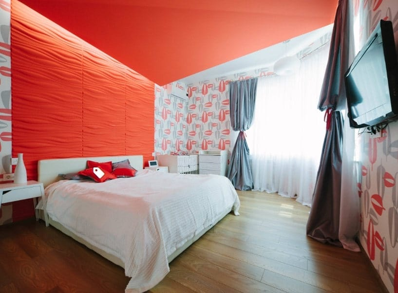 Primary bedroom featuring an orange ceiling and wall, along with hardwood flooring. The room has a large white bed set and a widescreen TV set on the wall.