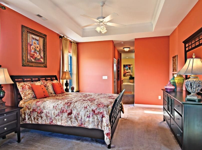 Primary bedroom featuring orange walls and a white tray ceiling, along with carpeted flooring. The room offers a classy bed with table lamps on both sides.