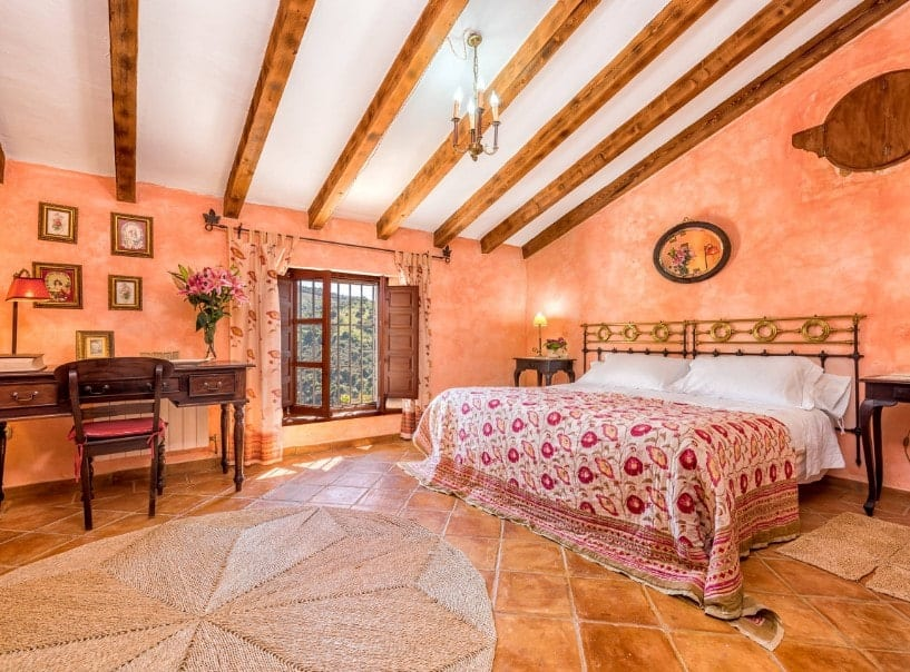 A spacious primary bedroom featuring orange walls and brown tiles flooring, along with a ceiling with beams. The room offers a large cozy bed and a classy desk and chair set.