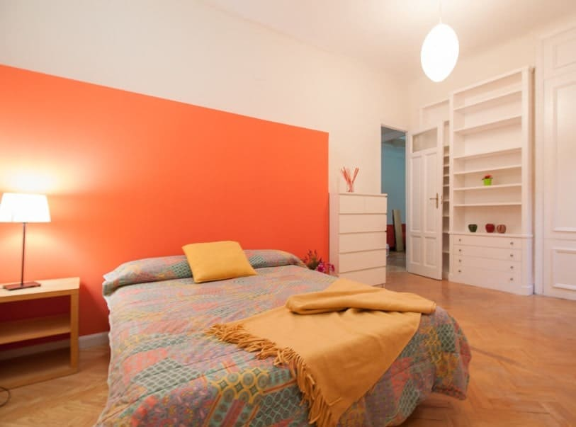 A spacious primary bedroom with stylish hardwood flooring and an orange wall. The room features a comfy bed and built-in shelving and drawers.