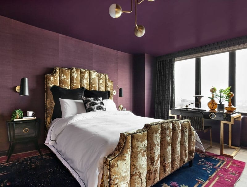 A close up look at this primary bedroom's stylish camouflage-style bed frame with a cozy bed setup lighted by two black wall lights on both sides. The room features a purple ceiling and purple walls.