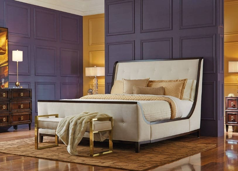 A focused shot at this primary bedroom's large classy bed along with elegant gold and purple combination walls and shiny hardwood floors.