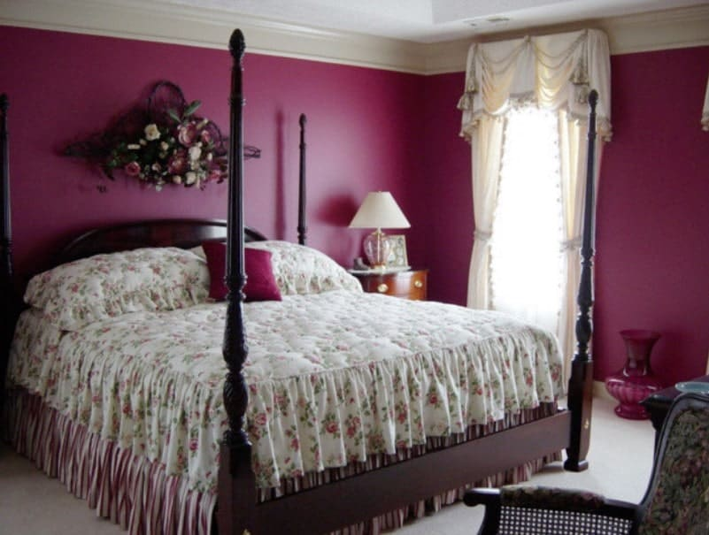 A focused shot at this primary bedroom's large classy bed set surrounded by purple walls, carpeted flooring and a white regular ceiling.