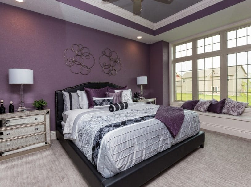 A primary bedroom boasting an elegant bed setup surrounded by gorgeous purple walls and a stunning purple tray ceiling.