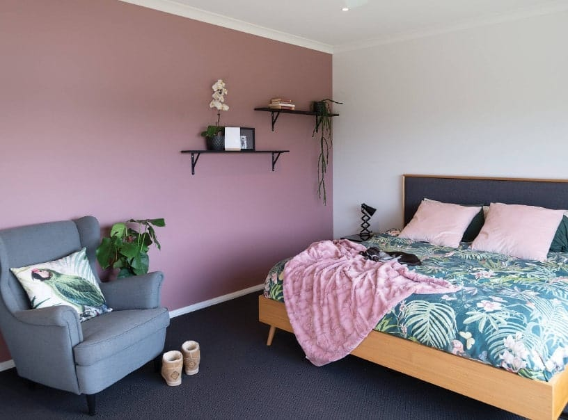 Primary bedroom featuring dark carpet flooring along with white and purple walls surrounding the large bed setup.