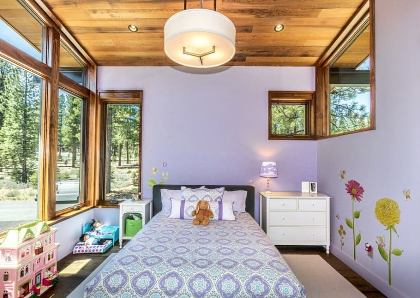 A primary bedroom with decorated purple walls, along with a wooden ceiling. The room offers a cozy bed with a table lamp on the side.
