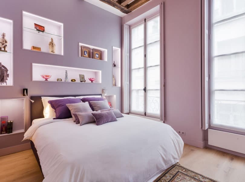 This primary bedroom features purple walls with multiple wall decors, along with hardwood flooring and a tall ceiling with beams.