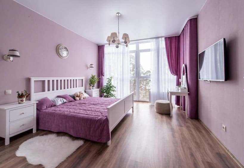 A primary bedroom featuring a large bed setup with a large widescreen TV in front, surrounded by purple walls and hardwood floors.