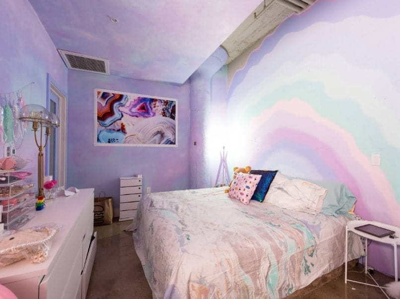 Primary bedroom with a large comfy bed along with a large white cabinet in front, surrounded by purple walls with artistic designs.